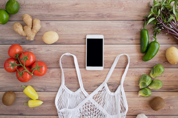 Mobile phone with the net eco bag and fresh vegetable on wood background. online grocery and organic farmer product shopping application. food and cooking recipe or nutrition counting.
