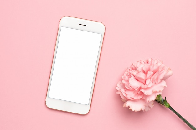 Mobile phone with pink carnation flower on a marble background