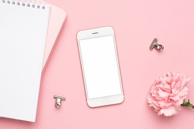 Mobile phone with pink carnation flower and notebook on a marble background