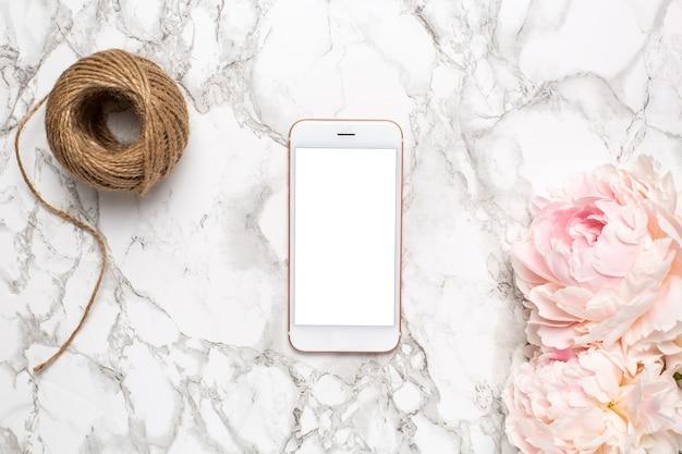 大理石の背景にパイオニーの花とひもが付いた携帯電話、休日のコンセプト-バレンタインデー、女性の日、母の日。花の上面図と植物学と装飾