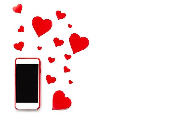 Мобильный телефон с красными сердечками, как лайки на белом фоне.