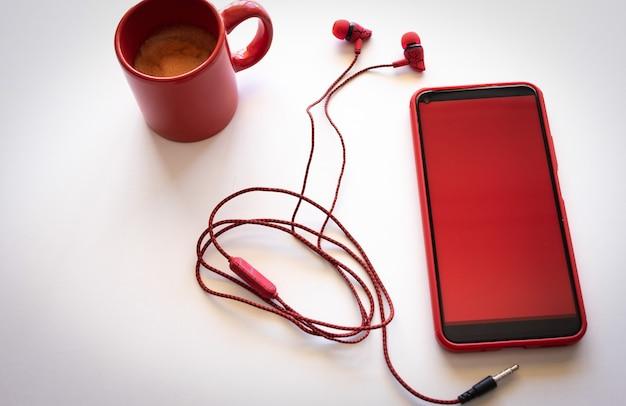 Мобильный телефон с красным экраном на белом фоне, красной кофейной чашкой и наушниками