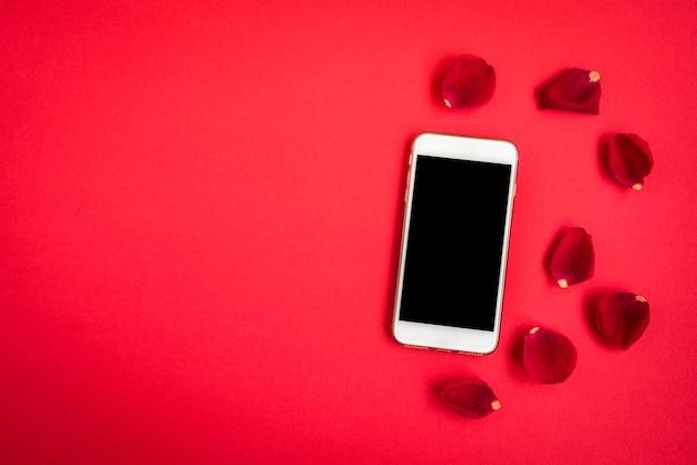 Мобильный телефон с лепестками роз на красном.