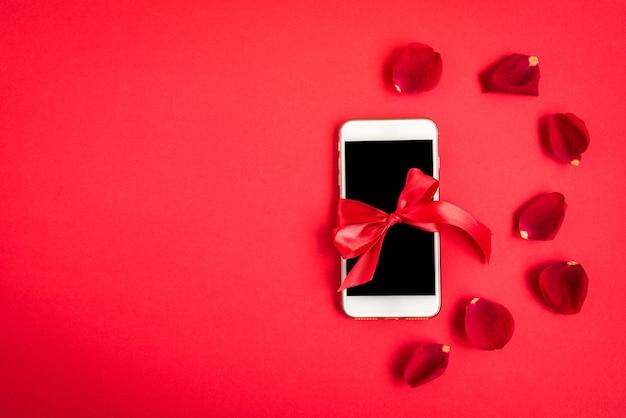 赤のバラの花びらを持つ携帯電話。