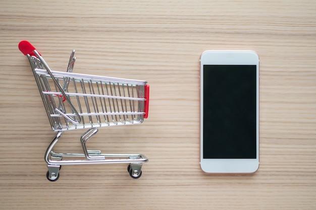 木製のテーブルの背景にオンラインショッピングの概念のショッピングカートと携帯電話