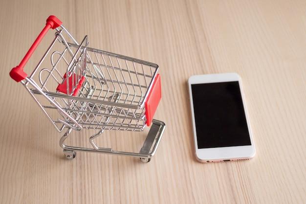 木製テーブルの背景ショッピングオンラインコンセプトのショッピングカートと携帯電話