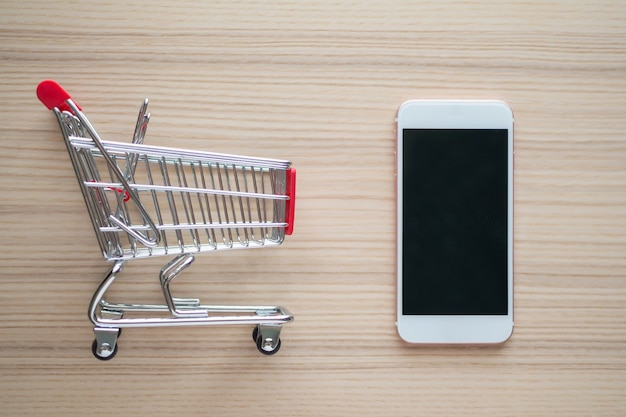 Mobile phone with shopping cart on wood table background shopping online concept