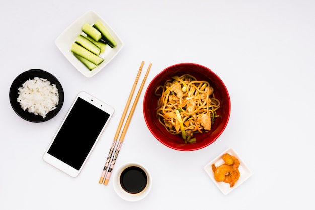 Mobile phone with tasty asian food over white surface