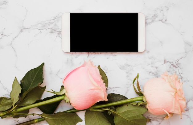 Mobile phone with two pink roses on marble backdrop