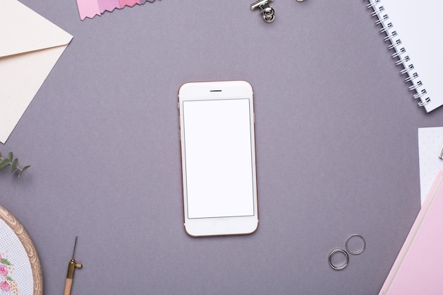 Mobile phone with white notepad , pink notebook and embroidery on grey