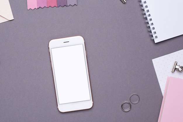 Mobile phone with white notepad , pink notebook and embroidery on grey to