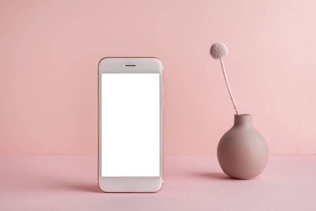白い画面と暗い影とピンクの背景に花瓶のドライフラワーと携帯電話。トレンド、コピースペースの側面図を備えた最小限のコンセプト
