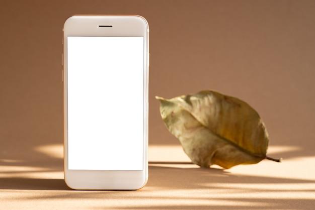 白い画面と暗い影の茶色の背景に乾燥した葉を持つ携帯電話。トレンド、コピースペースの側面図を備えた最小限のコンセプト