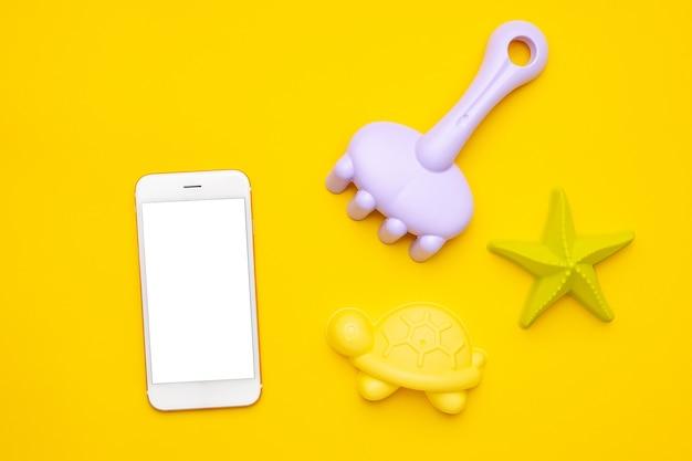 노란색 바탕에 흰색 화면과 플라스틱 해변 장난감 파스텔 색상이 있는 휴대전화. 미세 운동 개념의 개발. 창의력 게임, 기술 및 여름 개념입니다. 평면도