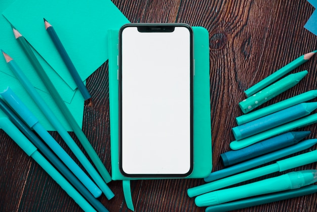 Mobile phone with white screen on diary near painting colors over wooden table