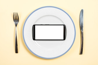 Mobile phone with white screen display on plate with fork and butterknife against beige background