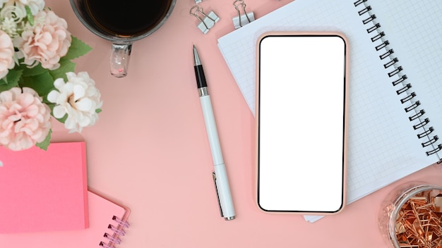 Mobile phone with white screen on female workspace.