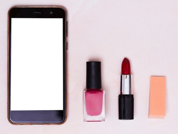 Mobile phone with white screen; nail varnish bottle; red lipstick and adhesive notes on colored backdrop