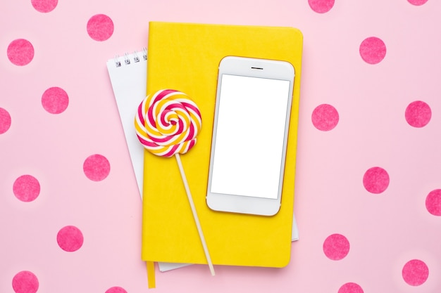 Mobile phone with a yellow notebook and colorful lolipop on a pink background with confetti top view