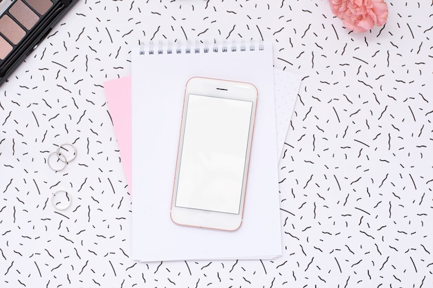 Mobile phone and women's notebook with cosmetics and flower