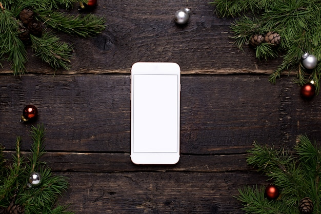 Mobile phone on a wooden table with a christmas tree and chrismas decoration