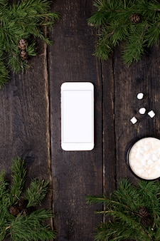 Mobile phone on a wooden table with a christmas tree and cocoa