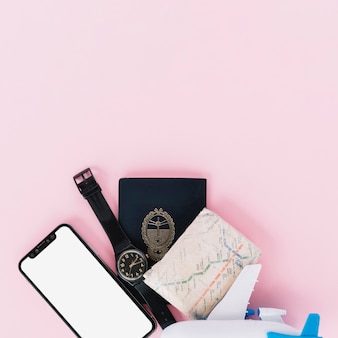 Mobile phone; wristwatch; passport; map and miniature airplane on pink background