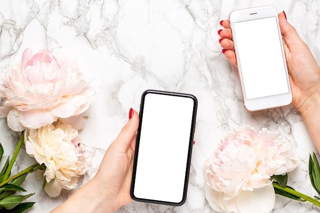 バレンタインデー、女性の日、母の日の休日の技術コンセプトを使用して、大理石の背景にパイオニーの花を持つ女性の手に携帯電話。植物相と装飾