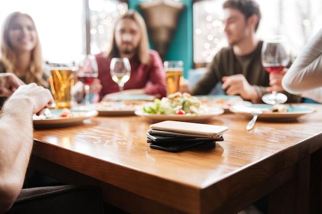 テーブルの上の携帯電話。カフェに座っている友人。