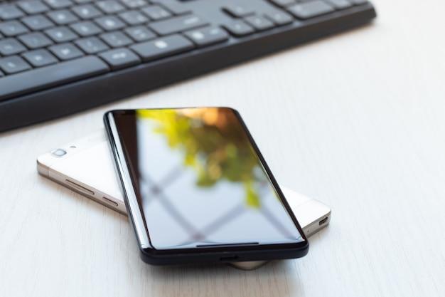 ワイヤレスでバッテリー充電を共有するテーブルの上に携帯電話を重ねて