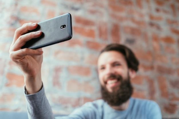 モバイル写真。テクノロジーとデジタルデバイス。電話を使用して自分撮りをしている男。
