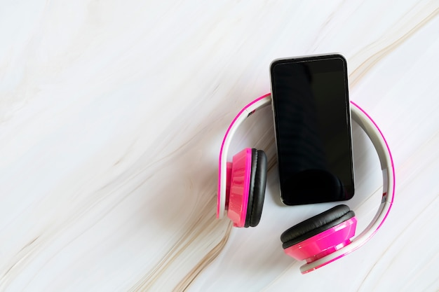 Mobile and pink headphone on white marble table with free copy space for text.