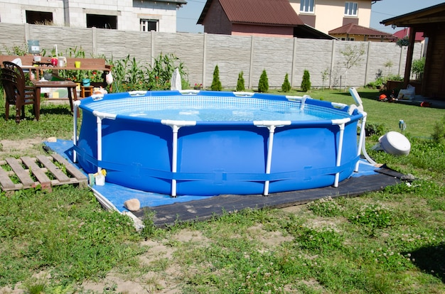 Mobile pool in the backyard, on the pool, round outdoor pool for the whole family on the lawn in summer,