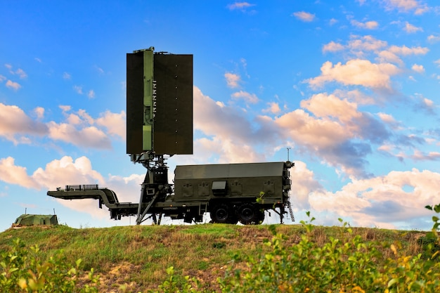 The mobile radar of military aviation stands on a hill against the background of a blue sky with beautiful clouds