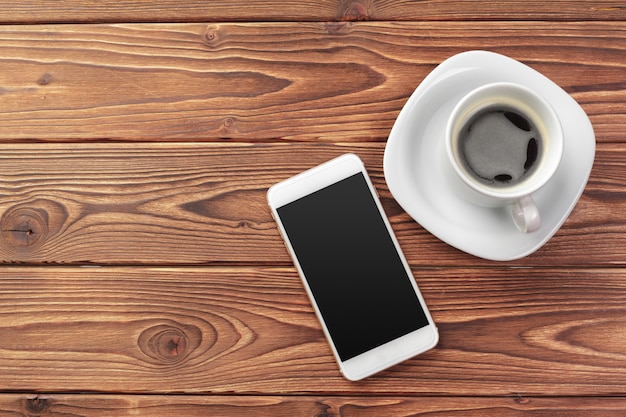 Mobile smart phone and a cup of coffee on wood texture background