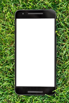 Mobile smart phone mockup with white screen on green grass background.
