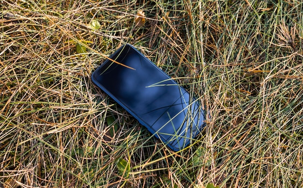 芝生の上の携帯スマートフォン-紛失した電話