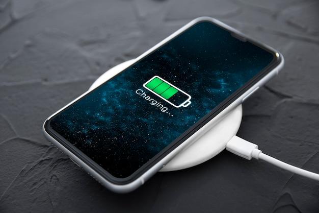 어두운 배경의 무선 충전 장치에 있는 모바일 스마트 폰. 화면의 아이콘 배터리 및 충전 진행 상황 조명.스마트폰이 전원에 연결되어 있습니다.배터리 수준이 낮은 문제가 있습니다.전화가 연결되었습니다.