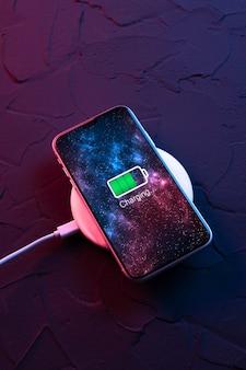 어두운 네온 빨간색과 파란색 배경에 무선 충전 장치의 모바일 스마트 폰. 아이콘 배터리 및 화면의 충전 진행 조명. 전원에 연결된 스마트폰. 배터리 부족