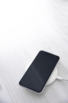 흰색 바탕에 무선 충전 장치에 모바일 스마트 폰. 아이콘 배터리 및 화면의 충전 진행 표시등.스마트폰이 전원에 연결됨.배터리 수준이 낮은 문제.플러그된 전화