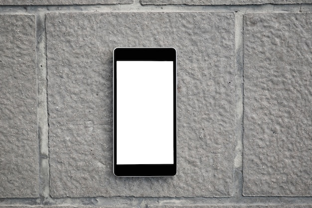Mobile smart phone with blank screen on concrete brick plate. technology and lifestyle concept.