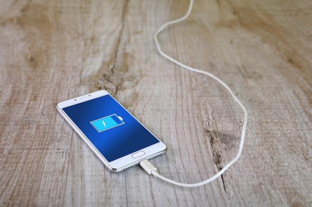 Мобильные смартфоны заряжаются на деревянном столе
