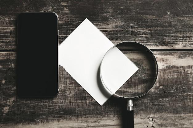 Smartphone mobile, lente d'ingrandimento e foglio di carta bianca isolato sul tavolo in legno fattoria nera concetto di gioco misterioso detective.