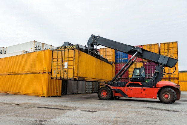 Mobile stacker handler in action at a container terminal.