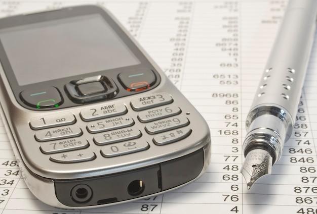 紙に携帯電話とペン