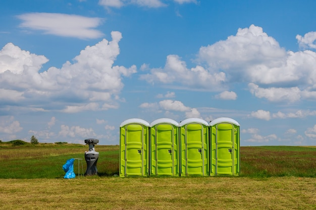 Mobile toilet. portable toilet on the grass on a background of clouds.