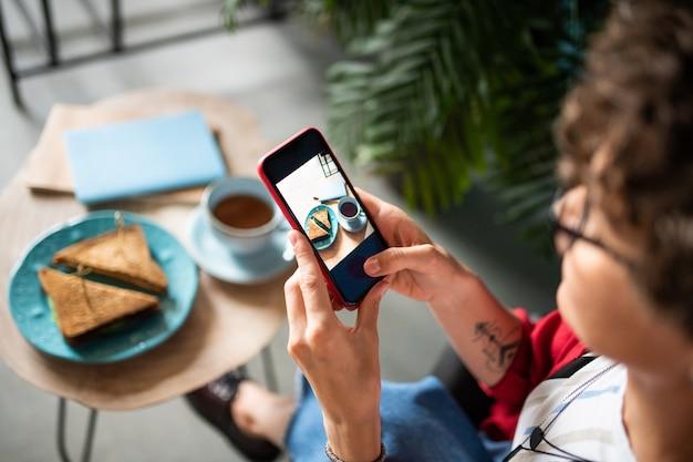 カフェに座っている間彼女のスマートフォンを使用してサンドイッチのショットを取り、テーブルで飲むモバイル女性