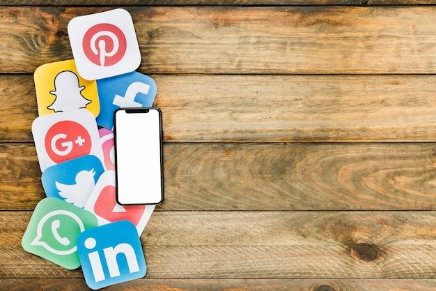 空白の画面を持つ携帯電話は、ソーシャルネットワーキングのアイコンを木製のテーブル上に配置