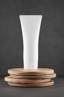 Косметическая трубка mocap на сером фоне. трубка стоит на деревянной подставке. 3d визуализация.