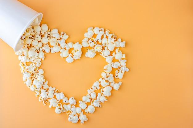 Люблю фильмы концепцию. попкорн в бумажной коробке разбросал на оранжевом фоне в форме сердца вид сверху, скопируйте пространства для текста. кино закусочная концепция. коробка для попкорна mocap